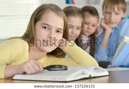 boy and three girls doing homework together at the table at home - stock photo