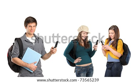 Boy and two beautiful girls sending messages by mobile phone isolated on white background with only the boy in focus. - stock photo