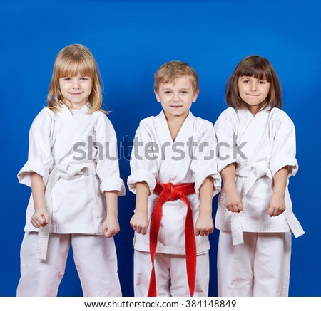 Boy and two girls are standing in the rack karate - stock photo