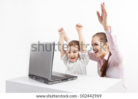 Boy and woman sitting by laptop. They are very happy. A new technology and child. - stock photo