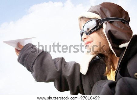 Boy as an old style pilot holding a paper airplane - stock photo