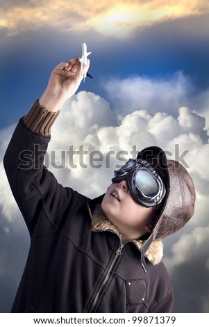 Boy as an old style pilot holding a toy airplane, heaven background