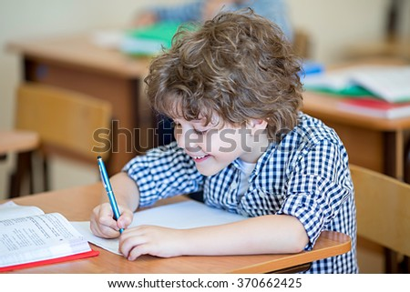 Boy at a desk in classroom - stock photo