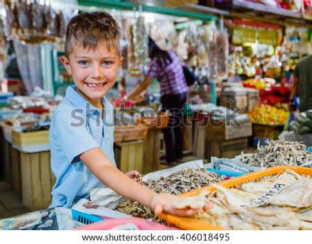 Boy at fish market - stock photo