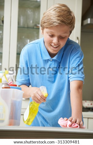 Boy At Home Helping to Clean Kitchen