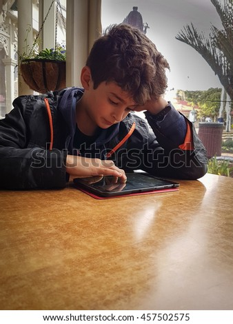Boy at table in low light in front of window resting  on his elbow concentrating with hand poised over his mobile device vignette