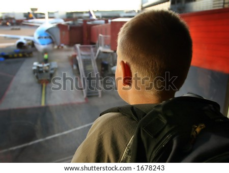 Boy at the airport looking outside, Focus on the face - stock photo