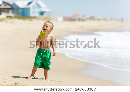 Boy at the beach with candy smiling - stock photo