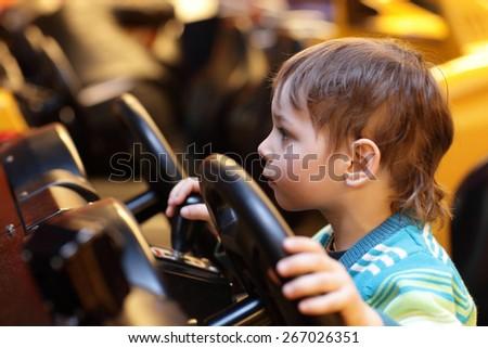 Boy at the wheel of car simulator at an amusement park - stock photo