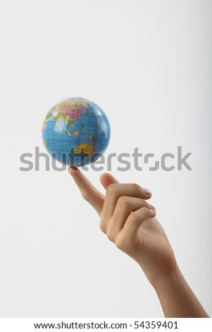 boy balancing a globe with the finger