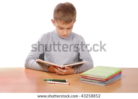 boy behind a table reads the book on white bacground