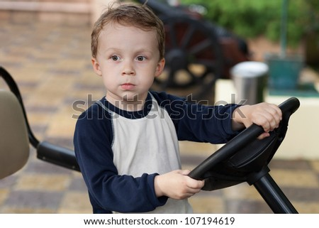 Boy behind the wheel of the electric vehicle - stock photo