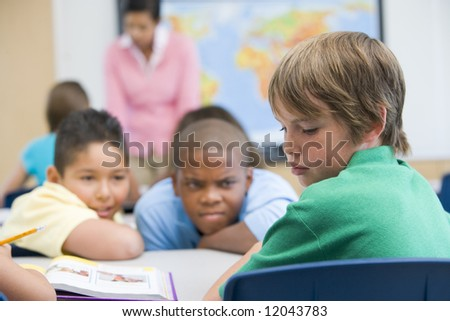 Boy being bullied in elementary school classroom - stock photo