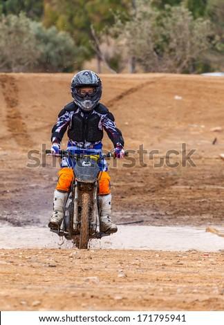 boy biker rides through the mud, sport background - stock photo