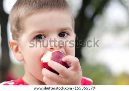 Boy bitten by a juicy red apple - stock photo