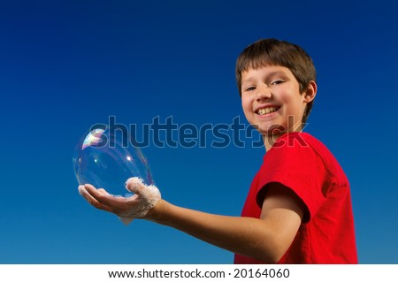 Boy blowing a bubbles and holding it in his hand with a perfect blue sky - stock photo