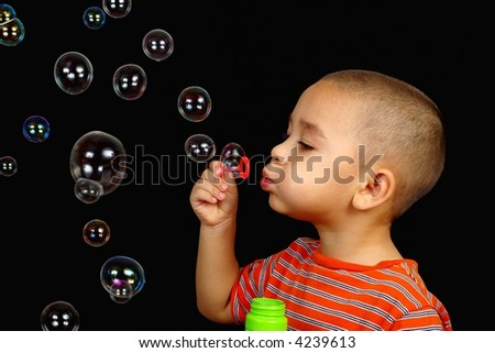 Boy blowing bubbles - stock photo