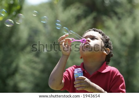 Boy blowing bubbles at the park - stock photo
