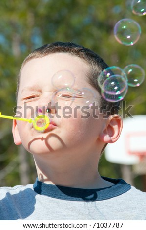 boy blowing bubbles on playground