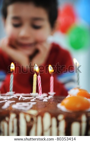 Boy blowing candles on cake, happy birthday party - stock photo