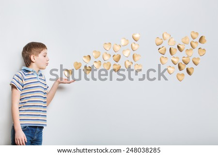 Boy blowing golden hearts from hand - stock photo