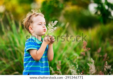 Boy blowing on a dandelion in the summer in the park on the green background