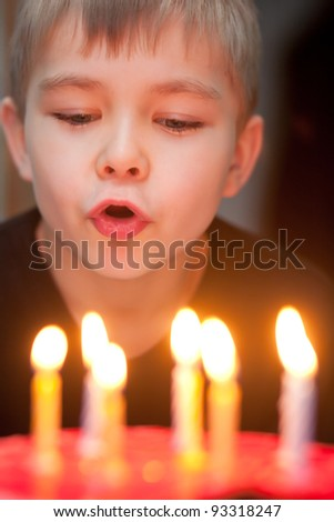 Boy blowing out candles for his birthday - stock photo
