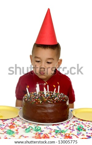Boy blowing out candles on a chocolate birthday cake - stock photo