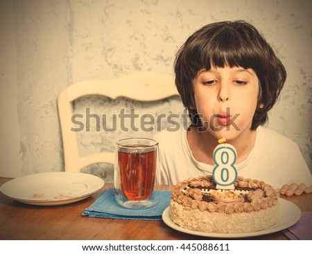 boy blowing out candles on birthday cake. digital eight. eight birthday. celebration. instagram image filter retro style - stock photo