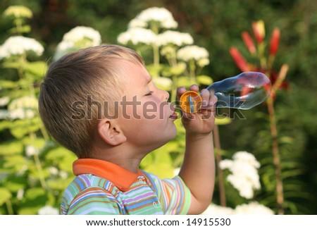 Boy blowing soap bubbles - stock photo