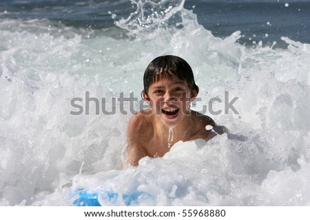 Boy body surfing in the sea - stock photo
