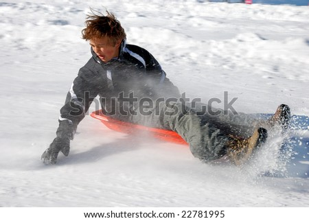 Boy braking while sledding down the hill with snow background
