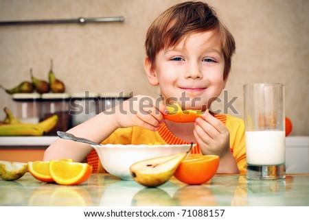 boy, breakfast, drinks milk, eats cereal and orange - stock photo