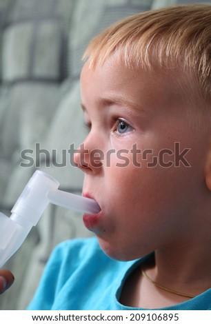 boy breathes through inhaler - stock photo