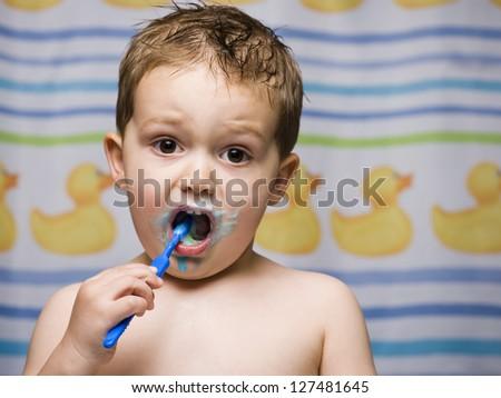 Boy brushing teeth in bathroom - stock photo
