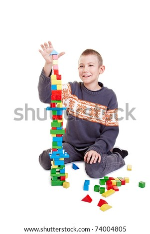 Boy building carefully a tower with building bricks - stock photo