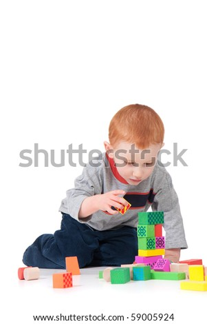Boy building colorful block tower. Isolated on white with shadows.