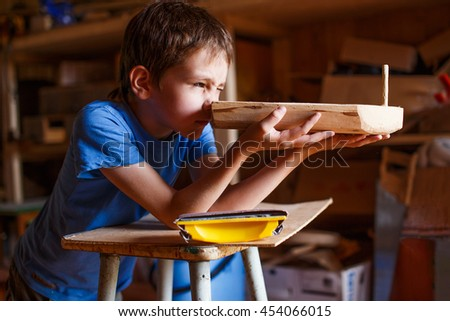 boy builds a toy ship of wood. child in the workshop makes crafts. toy boat of wood