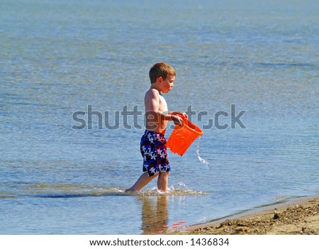 boy carrying a bucket of water at the beach