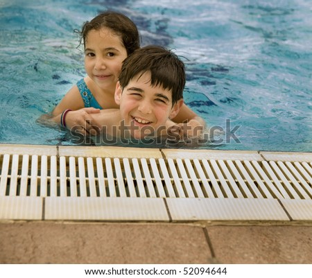 Boy carrying girl by piggyback in the pool - stock photo