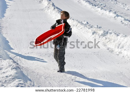 boy carrying his sled down the hill with snow background