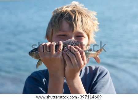 Boy caught grayling and shows all your catch - stock photo