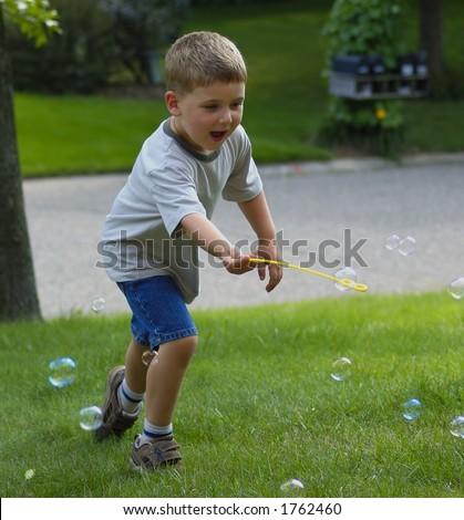 Boy Chasing Bubbles - stock photo