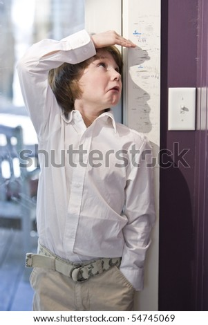 Boy checking height on growth chart at home on doorframe