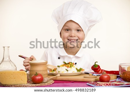 boy chef prepares rice with vegetables