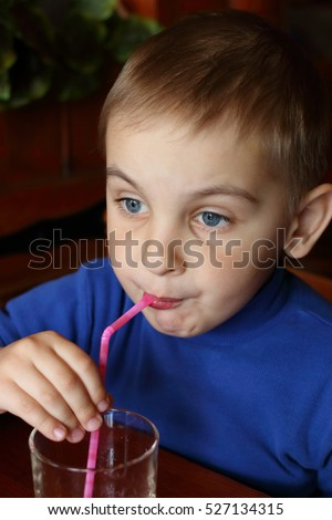 Boy child drinks from glass through straw  or tubule indoors in cafe