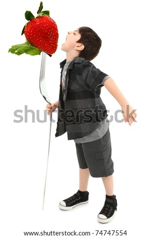 Boy Child Eating Giant Strawberry on Giant Fork with Clipping Path - stock photo