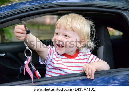 boy child sitting on the driver's seat in the car - stock photo