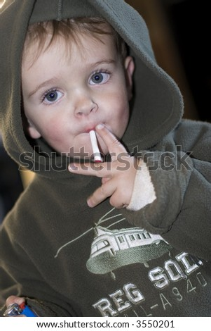 boy; child; smoking; smoke; puff; drag; cigarette; son; hood; blue; cute; young; offspring; health; unhealthy; danger; cancer; lung; drug; influence - stock photo