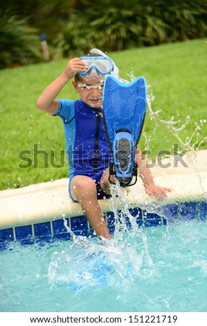 boy child splashing water with swimming flippers in summer on edge of pool - stock photo